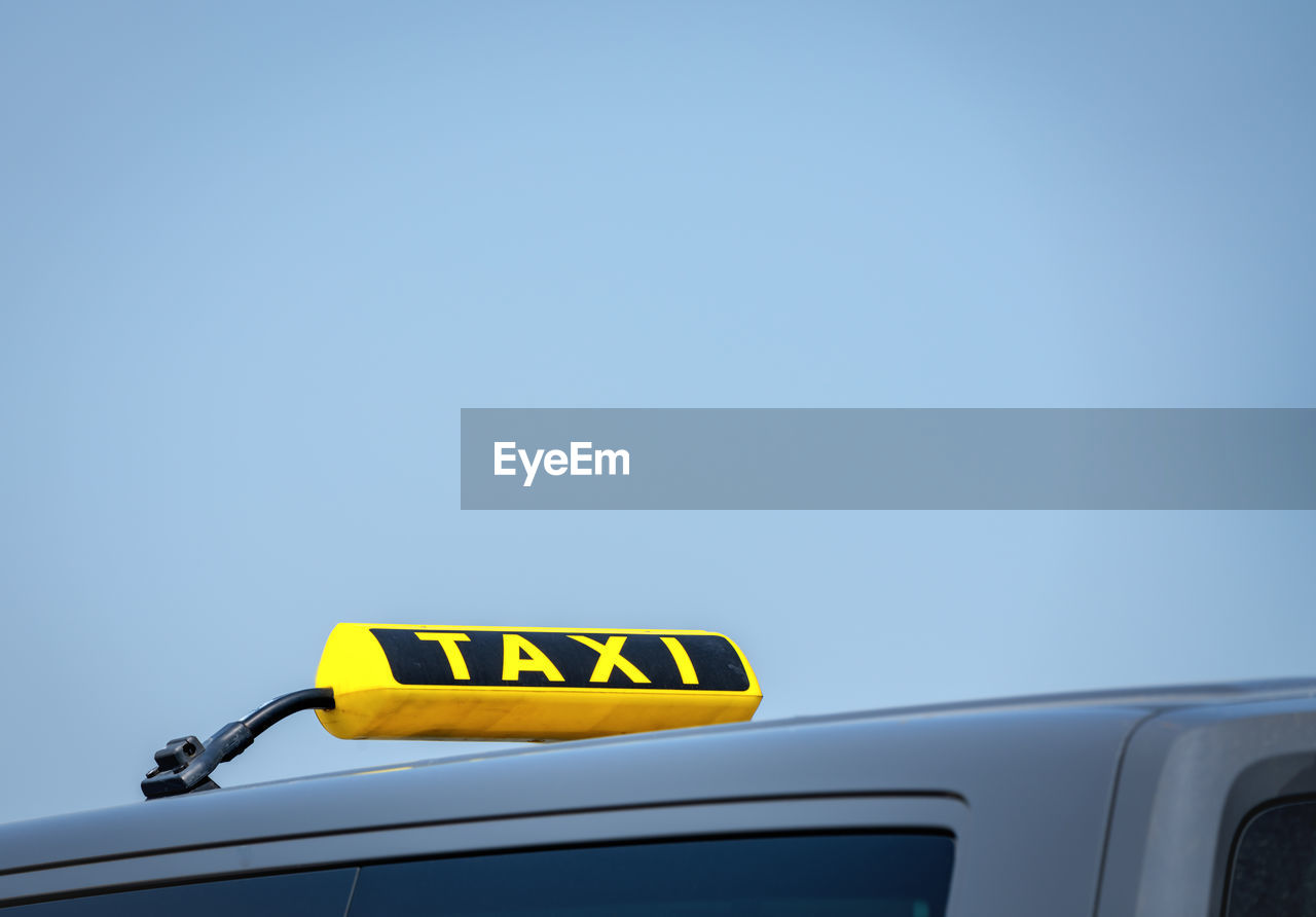 car, mode of transportation, text, western script, yellow, transportation, motor vehicle, land vehicle, copy space, clear sky, communication, car roof, blue, sky, taxi, day, no people, capital letter, sign, low angle view