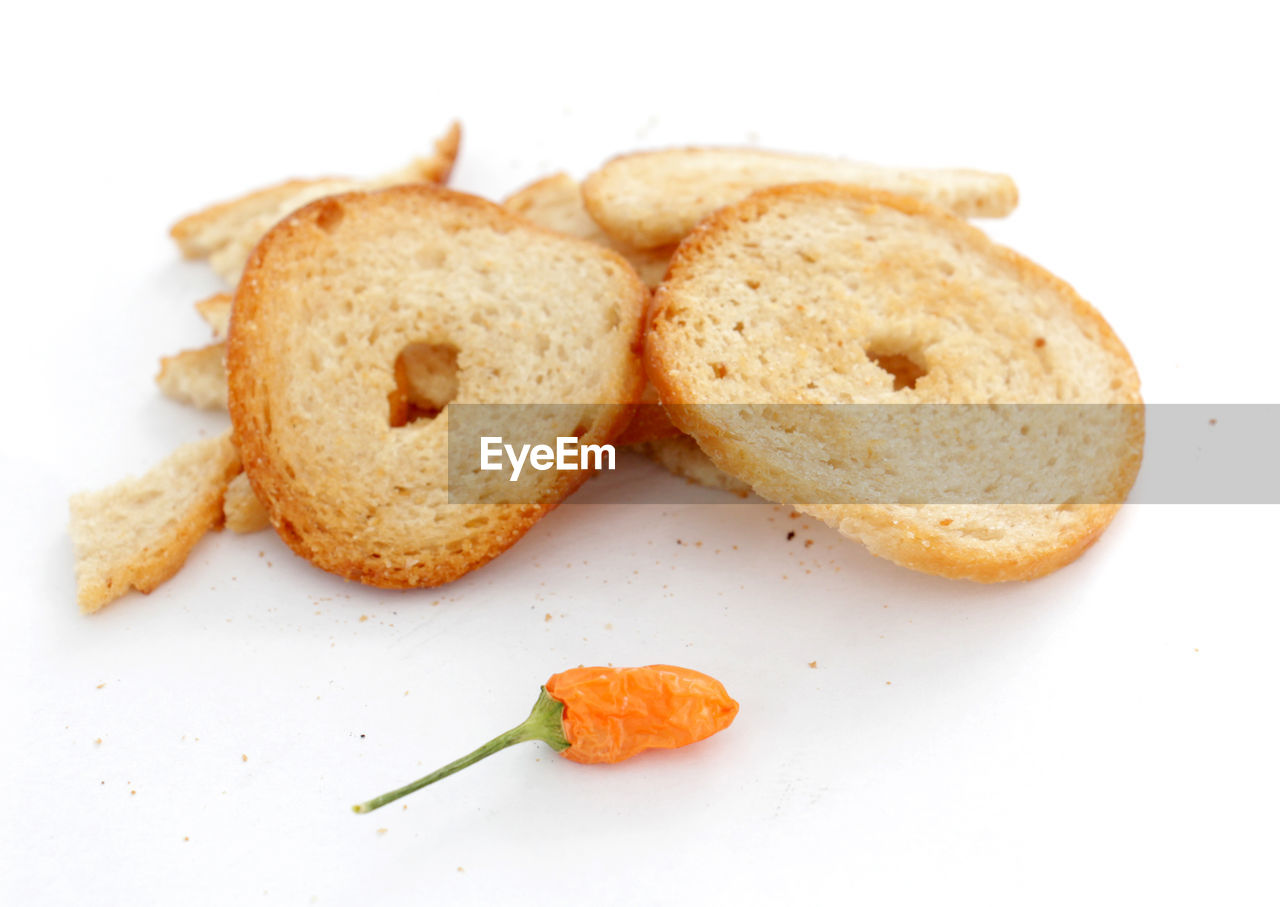 Close-Up Of Breads And Chili Pepper Against White Background