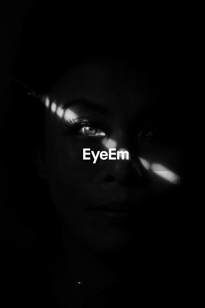 Close-up portrait of woman in darkroom