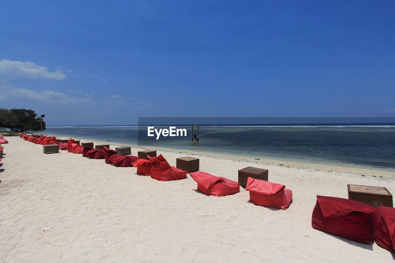 Row Of Empty Red Bean Bags And Tables On Beach Against Sky