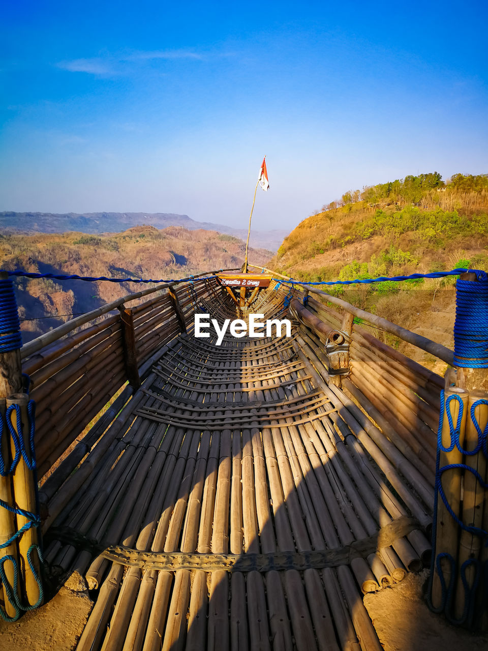 sky, nature, scenics - nature, beauty in nature, day, blue, wood - material, water, flag, tranquility, mountain, tranquil scene, railing, no people, non-urban scene, architecture, sunlight, outdoors, landscape