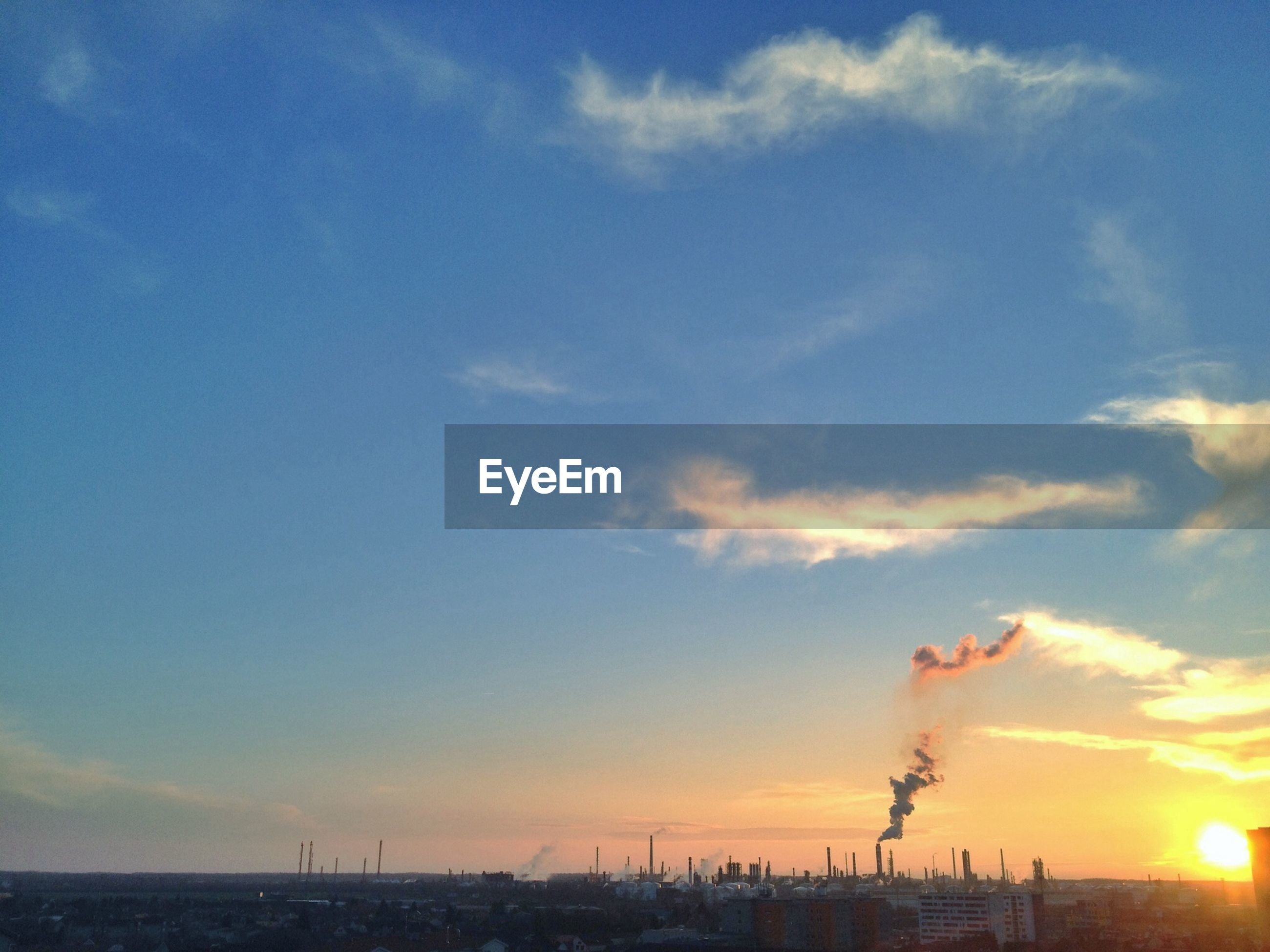 Cityscape with factory emitting smoke against sky at sunset