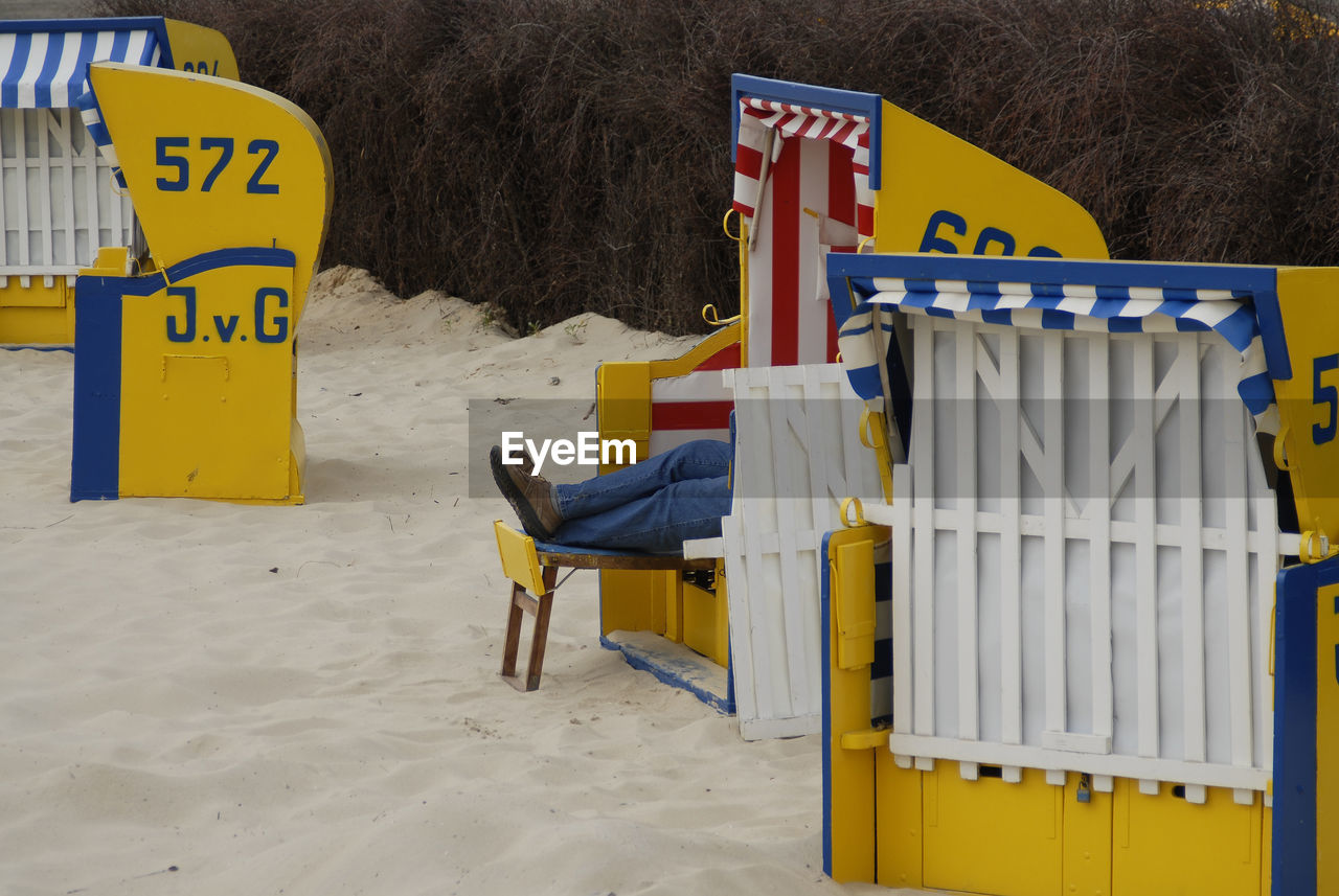 land, yellow, sand, beach, seat, one person, chair, day, nature, communication, relaxation, real people, text, western script, sitting, hooded beach chair, outdoors, garbage bin, leisure activity
