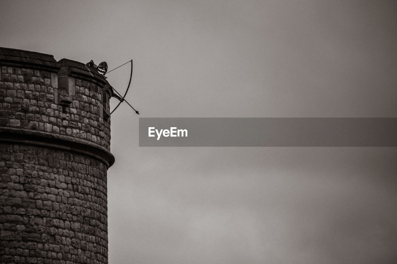 Low Angle View Of Archery On Tower Against Cloudy Sky At Dusk