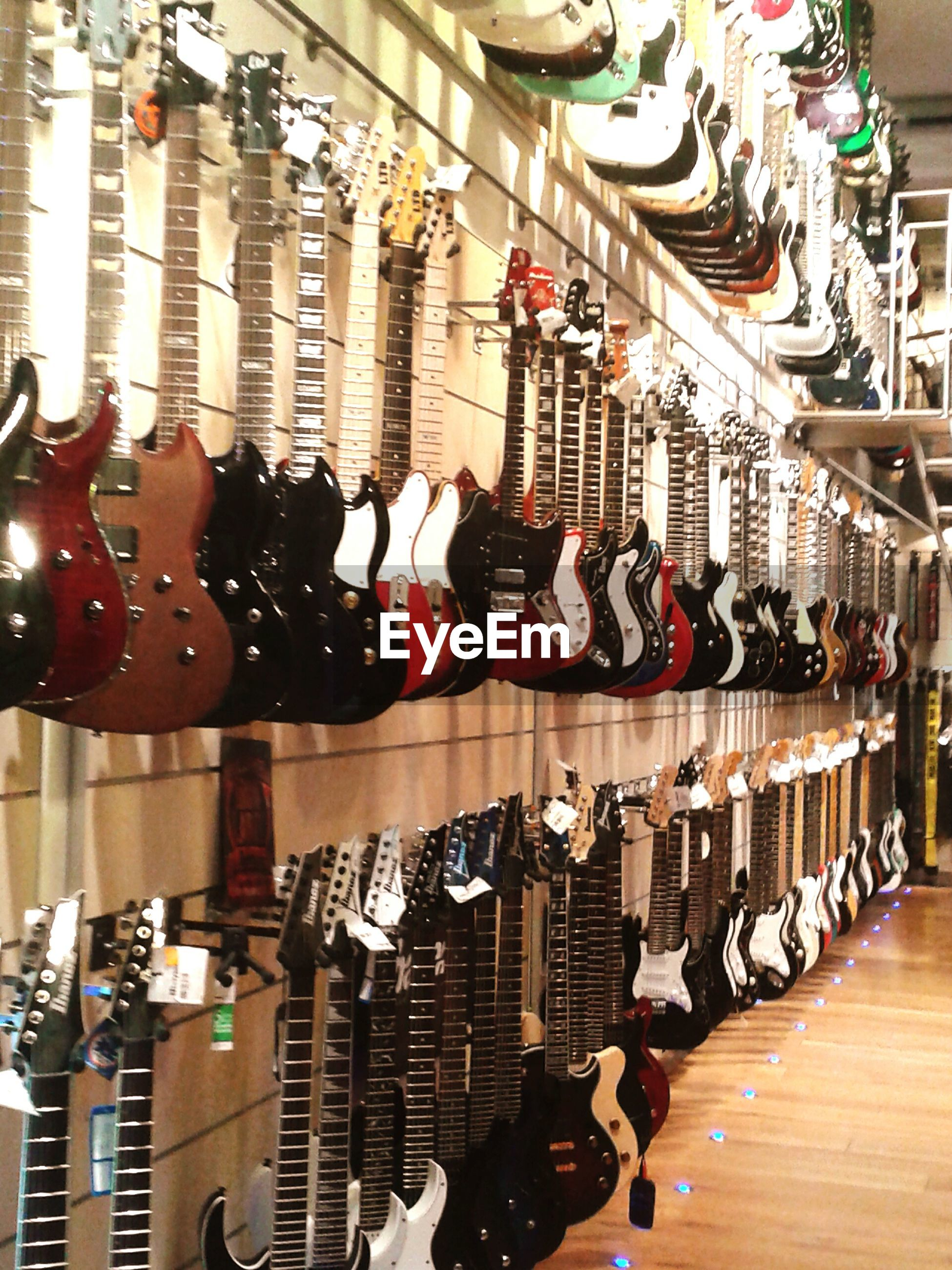 indoors, large group of objects, in a row, retail, variation, choice, abundance, arrangement, order, for sale, store, shopping, market stall, repetition, market, collection, hanging, side by side, large group of people
