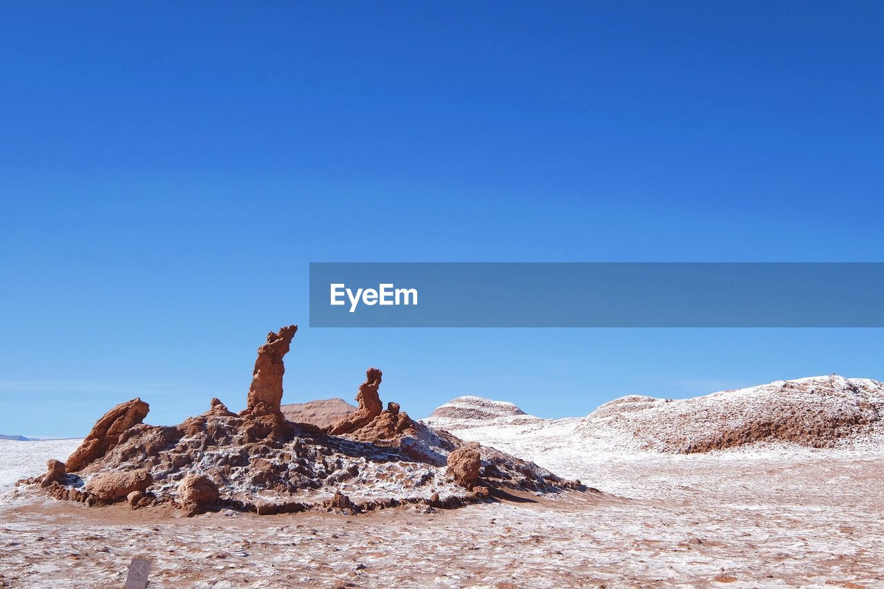 sky, clear sky, copy space, blue, real people, scenics - nature, solid, rock, rock - object, beauty in nature, tranquil scene, tranquility, nature, day, lifestyles, mountain, leisure activity, environment, non-urban scene, remote, outdoors, arid climate, climate