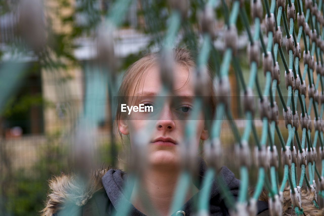 Portrait of serious girl seen through chainlink fence