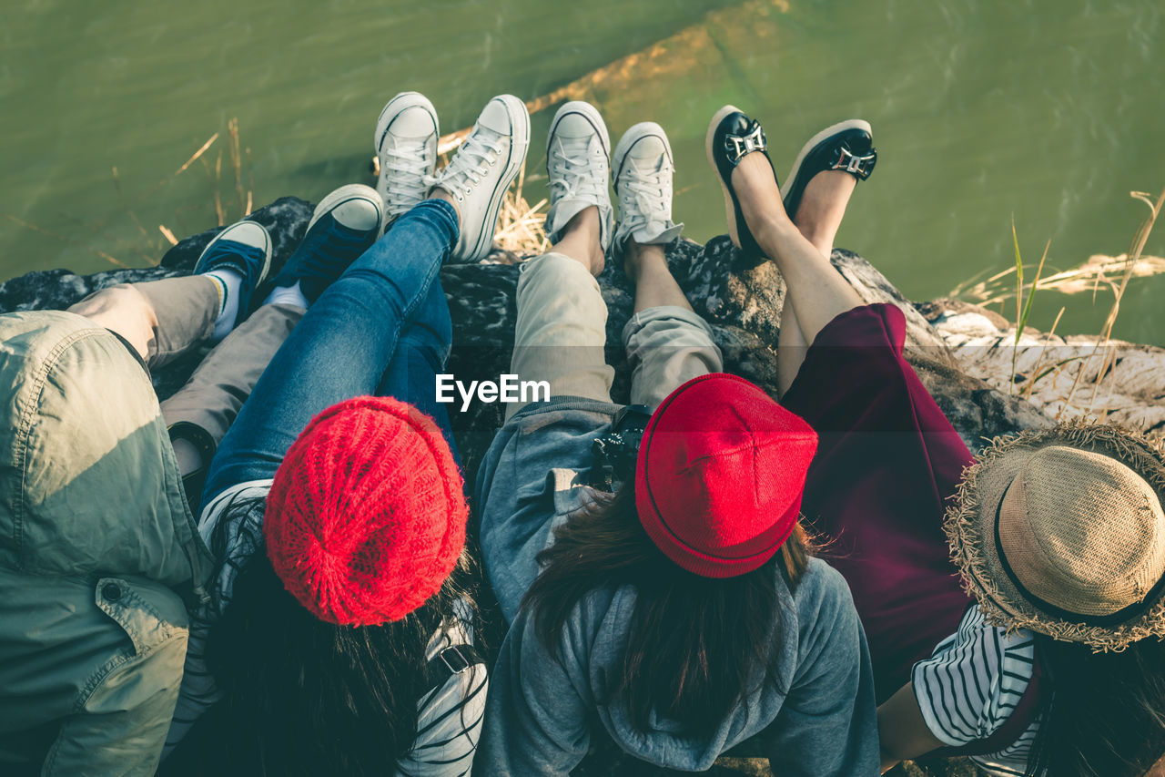 High Angle View Of Friends Sitting On Jetty Against Water