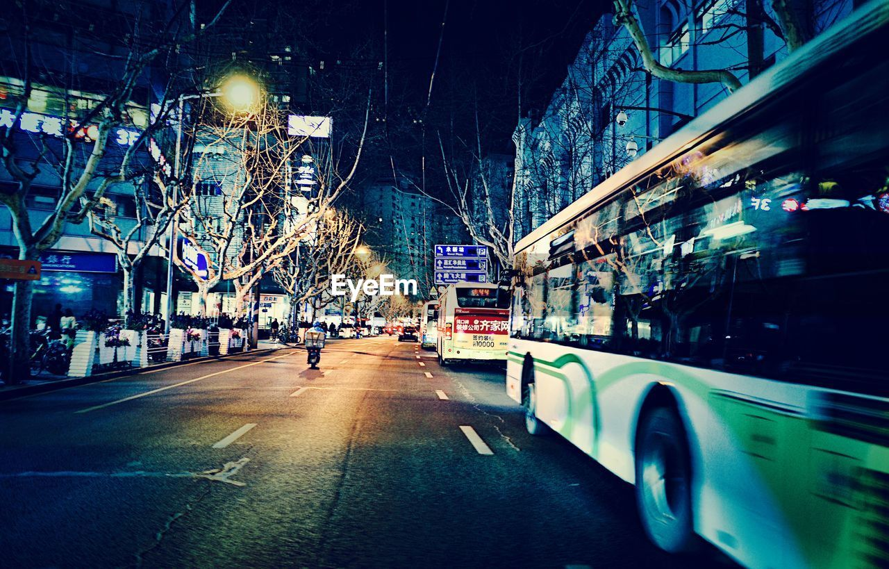 architecture, transportation, building exterior, built structure, mode of transportation, illuminated, city, night, land vehicle, street, motor vehicle, car, road, building, motion, city street, blurred motion, the way forward, no people, nature, outdoors