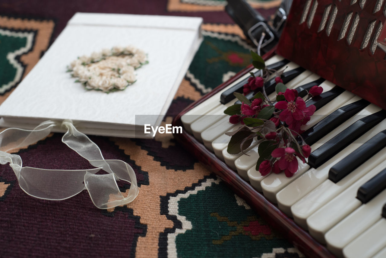 High angle view of harmonica keys and book with flowers
