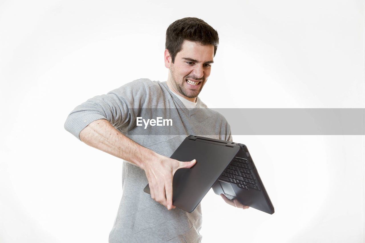 Man holding laptop while standing against white background