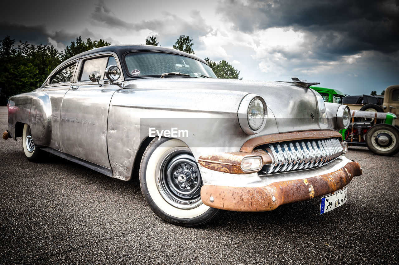 car, motor vehicle, mode of transportation, transportation, cloud - sky, retro styled, land vehicle, sky, vintage car, day, metal, stationary, old, nature, no people, front view, outdoors, rusty, headlight, silver colored, luxury, chrome