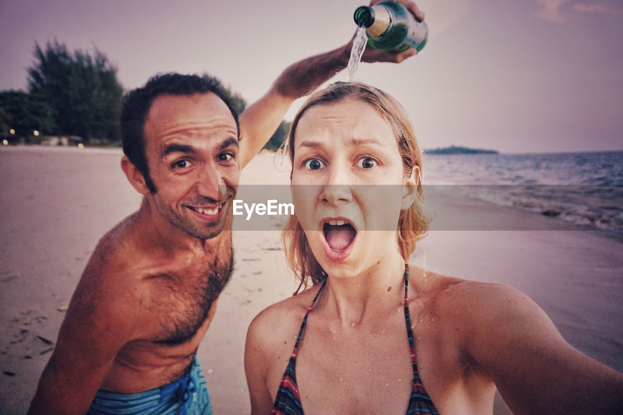 looking at camera, real people, leisure activity, portrait, front view, young adult, mouth open, two people, togetherness, shirtless, young women, outdoors, beach, young men, fun, lifestyles, happiness, water, making a face, smiling, vacations, standing, day, sky, sea, nature, friendship, people