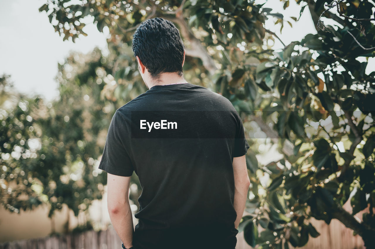 Rear view of man standing against trees