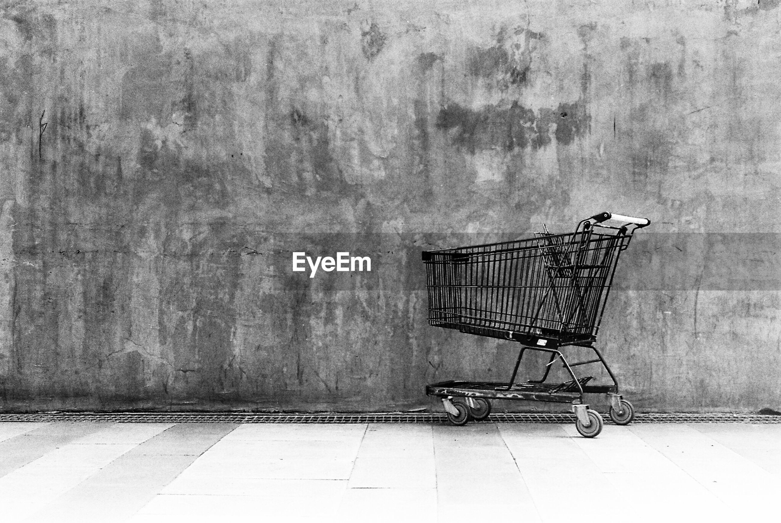 Abandoned shopping cart against wall