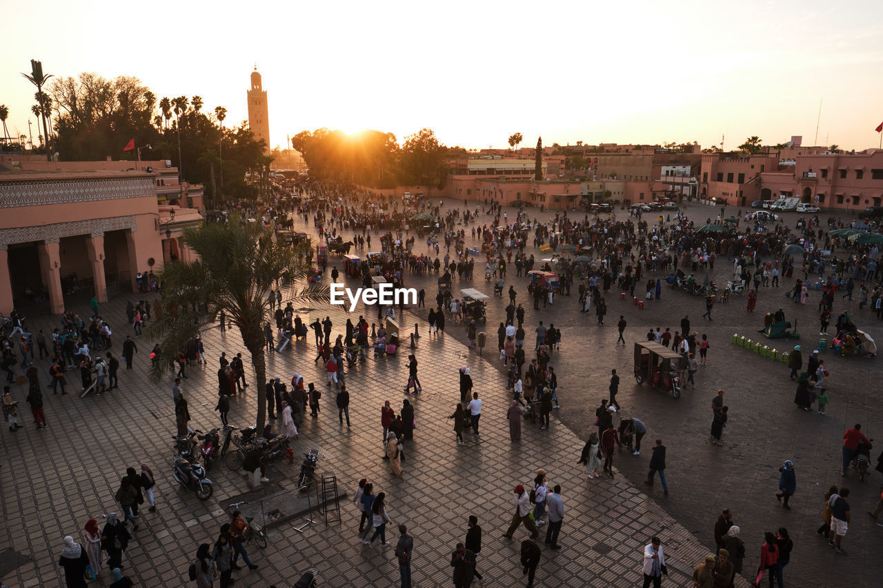 crowd, large group of people, architecture, group of people, real people, built structure, building exterior, city, street, men, sky, high angle view, travel, travel destinations, sunset, tourism, nature, women, town, outdoors, architectural column