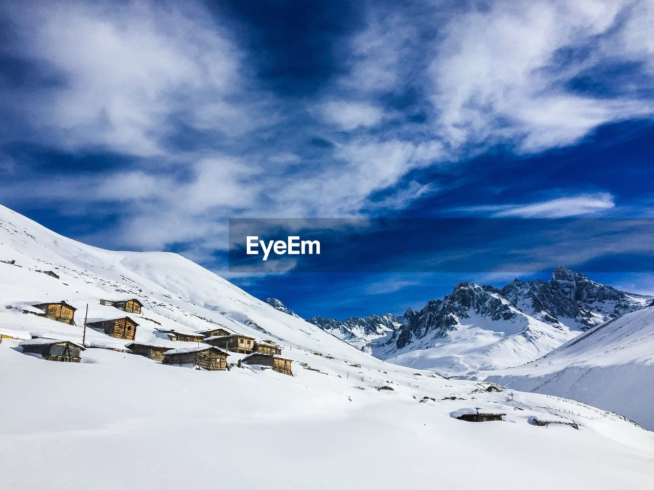 SCENIC VIEW OF COTTAGES ON MOUNTAIN IN WINTER