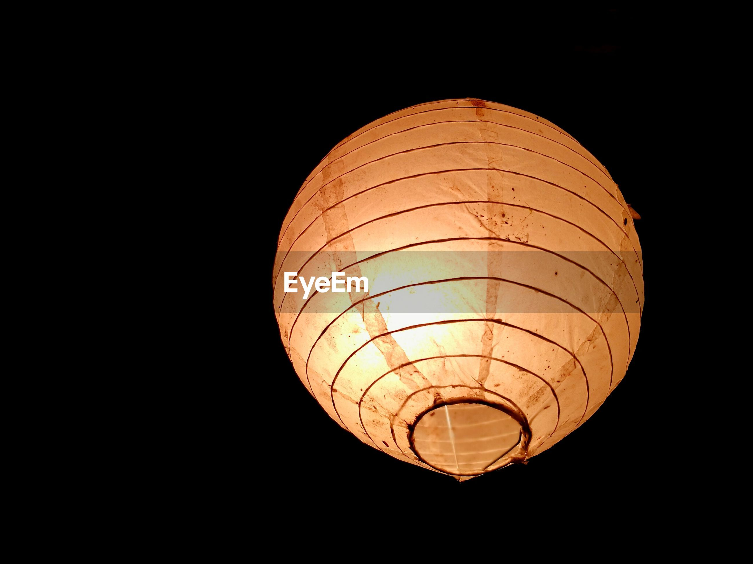 Low angle view of illuminated lantern against black background
