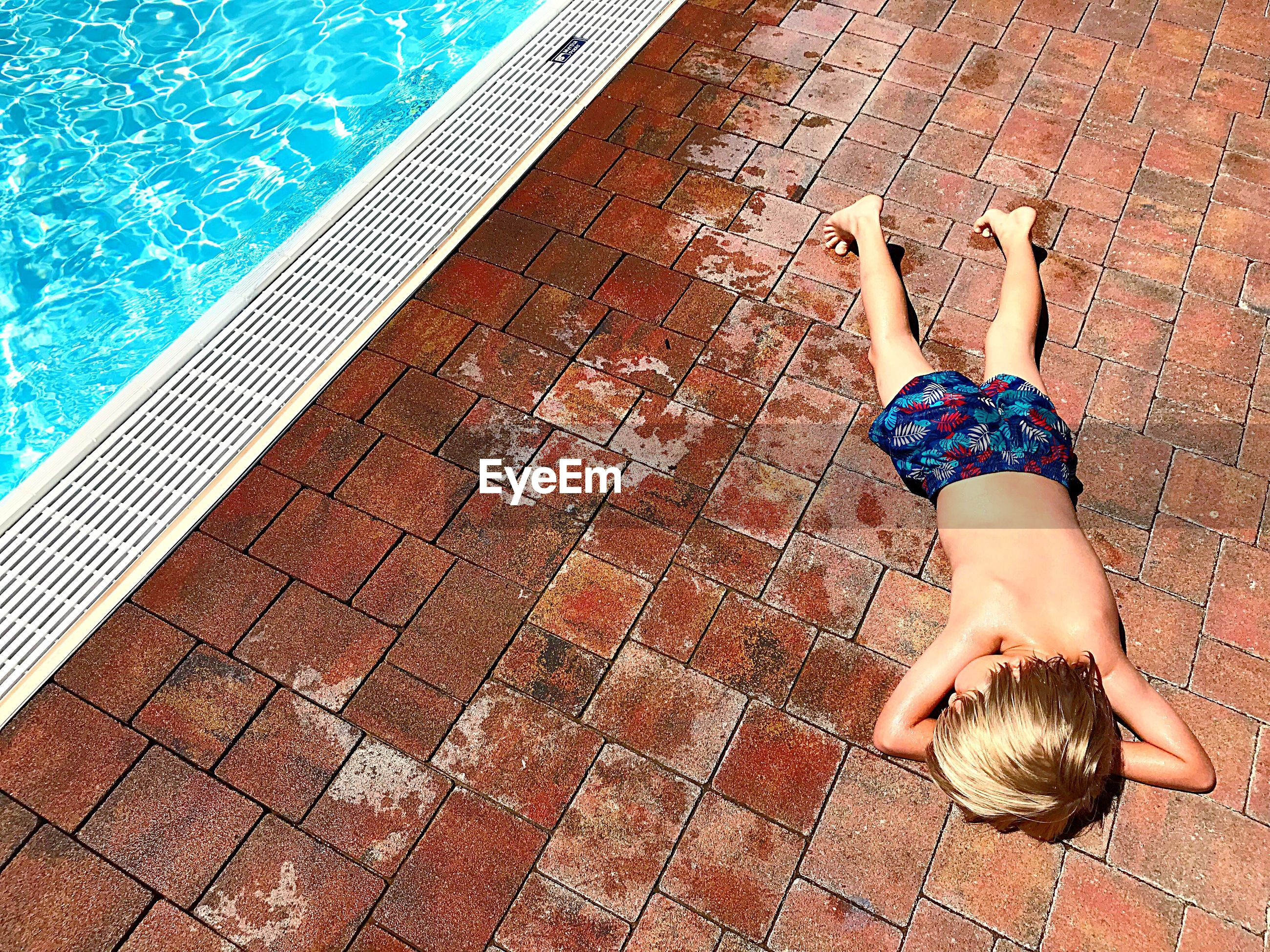 High angle view of shirtless boy relaxing by swimming pool