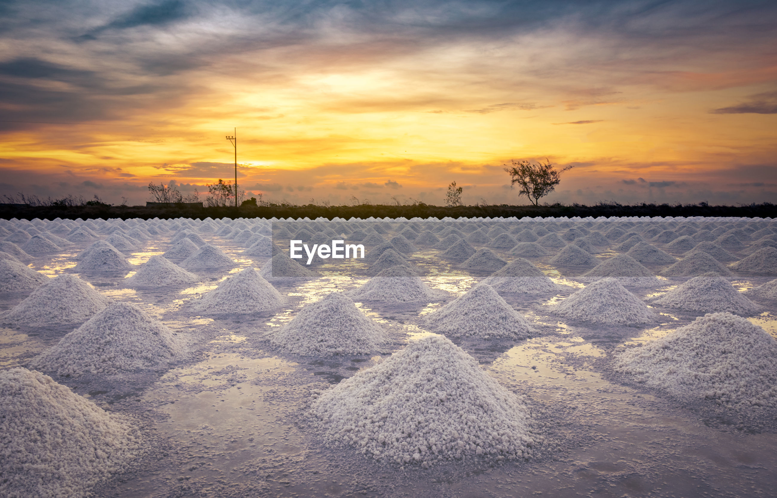 SCENIC VIEW OF SNOWY FIELD AGAINST SKY AT SUNSET