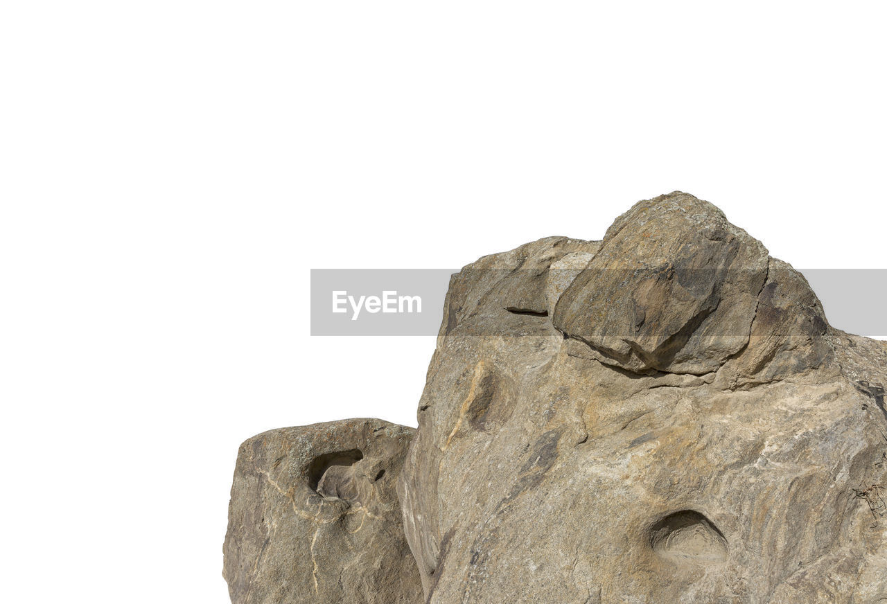 solid, copy space, rock, white background, studio shot, sky, no people, clear sky, rock - object, low angle view, nature, representation, close-up, human representation, textured, sculpture, rock formation, rough, art and craft, statue