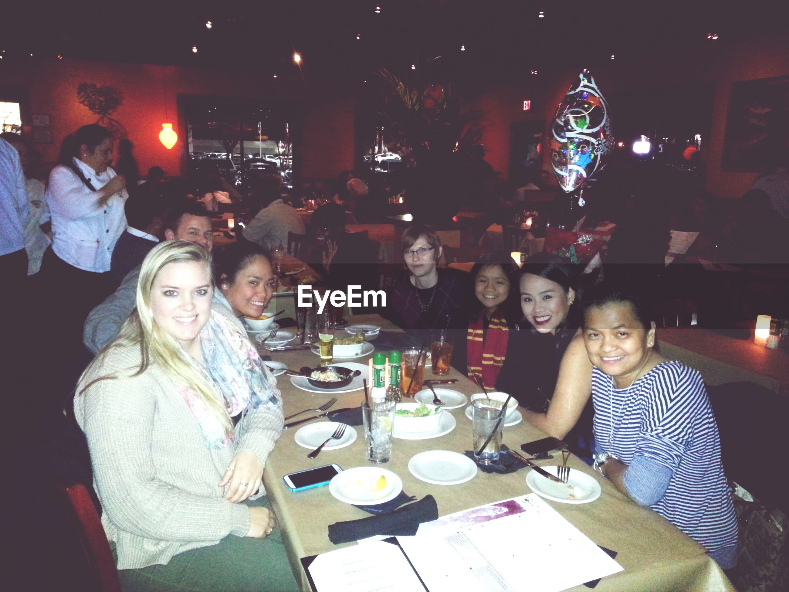indoors, lifestyles, table, food and drink, drink, leisure activity, illuminated, restaurant, casual clothing, holding, celebration, men, sitting, night, drinking glass, food, front view