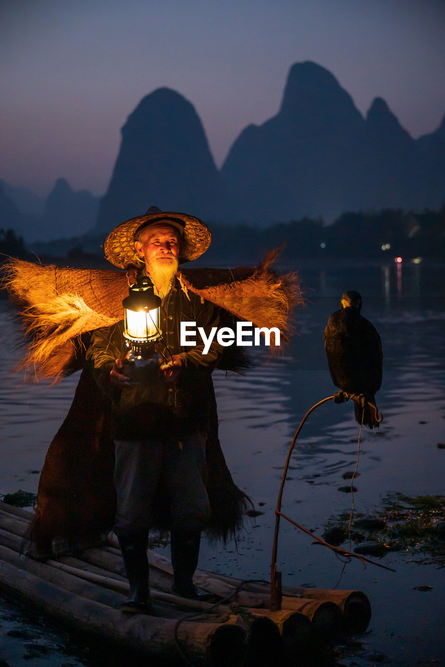 Man with lantern standing by bird on boat in lake against sky during sunset