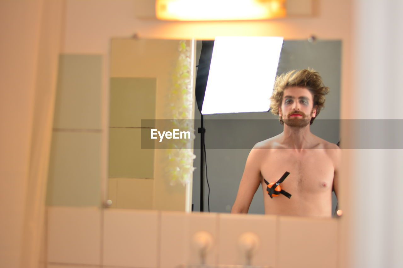 Portrait Of Shirtless Man With Face Paint And Duct Tape On Chest In Bathroom