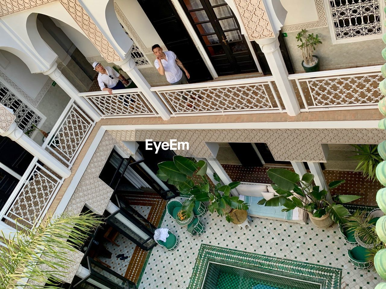 built structure, architecture, building exterior, plant, potted plant, staircase, window, building, high angle view, railing, steps and staircases, day, nature, women, group of people, growth, lifestyles, men, courtyard, houseplant