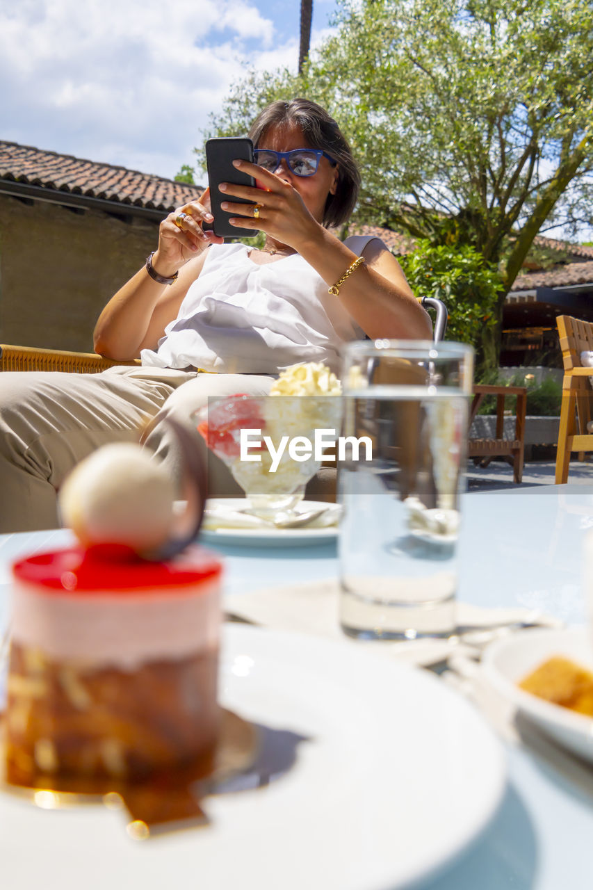 Low Section Of Senior Woman Using Phone Siting On Chair Outdoors
