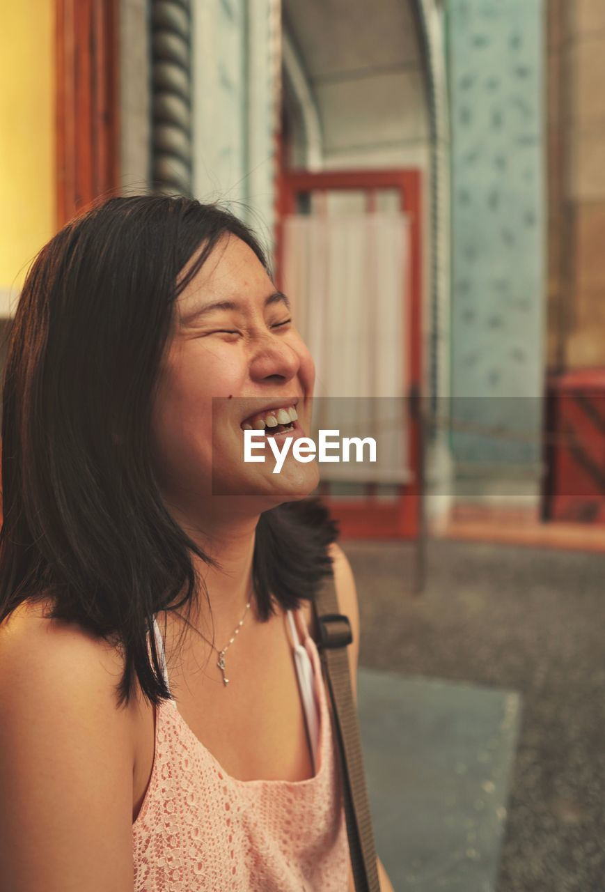 Cheerful young woman with eyes closed in city