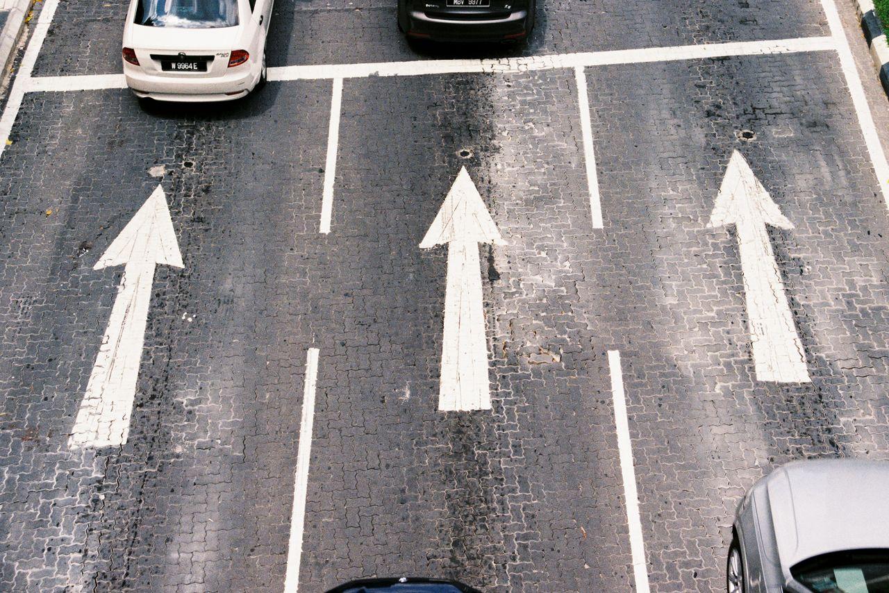 sign, arrow symbol, transportation, road, symbol, guidance, communication, marking, road marking, direction, street, city, directional sign, road sign, high angle view, day, mode of transportation, no people, car, traffic arrow sign