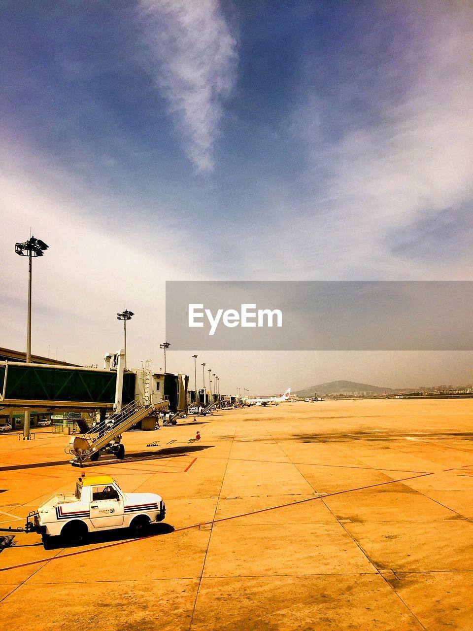 Vehicle on airport runway against sky