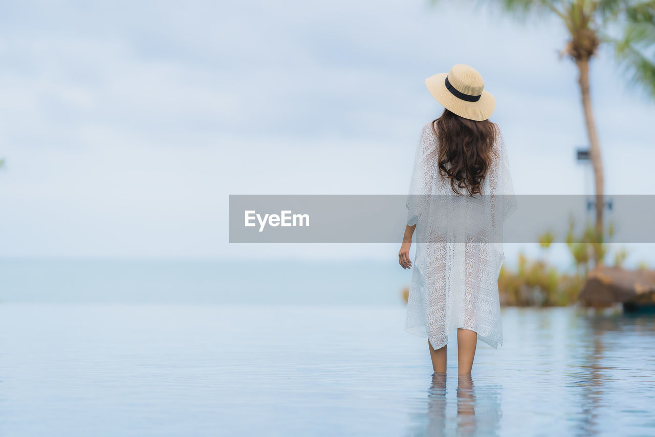 water, rear view, one person, hat, clothing, real people, women, leisure activity, sea, focus on foreground, lifestyles, day, standing, adult, hair, nature, full length, dress, fashion, hairstyle, outdoors
