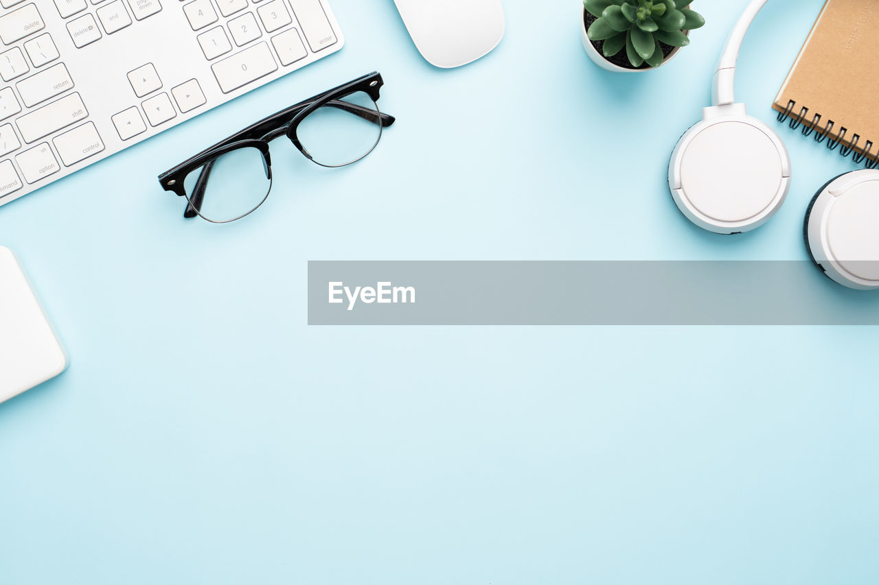 eyeglasses, glasses, still life, indoors, table, technology, copy space, no people, blue, pen, book, high angle view, close-up, connection, communication, publication, white color, writing instrument, computer equipment, directly above, keyboard