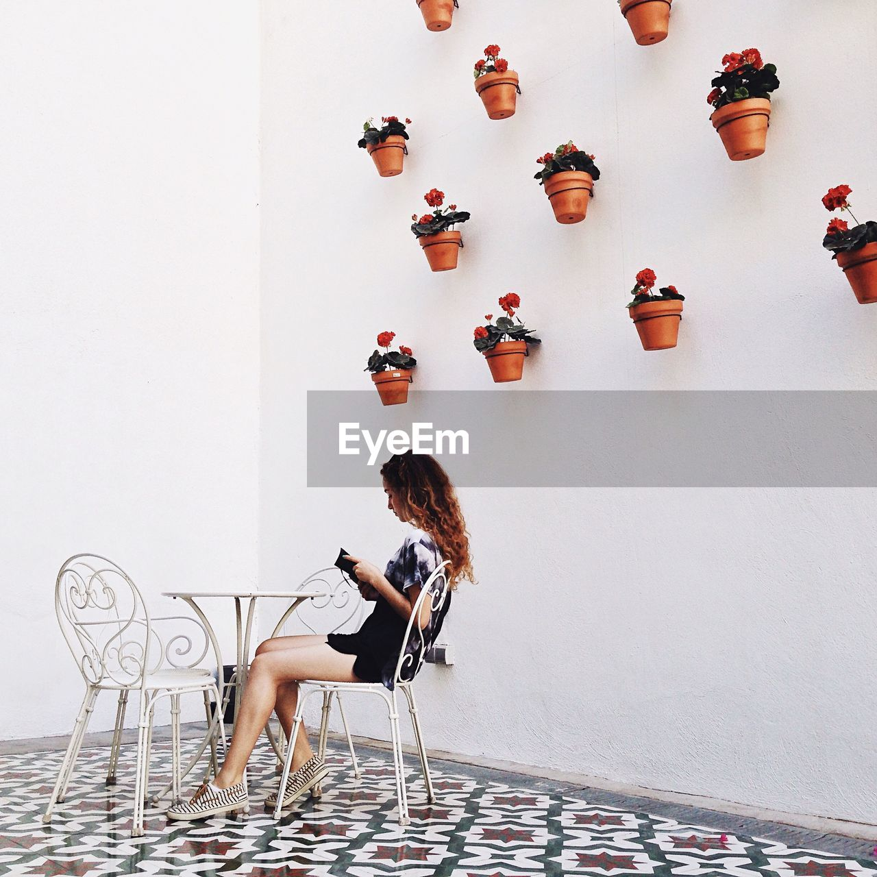 Side View Of Young Woman Sitting On Chair Looking At Menu Card Against Potted Plants On Wall Indoors