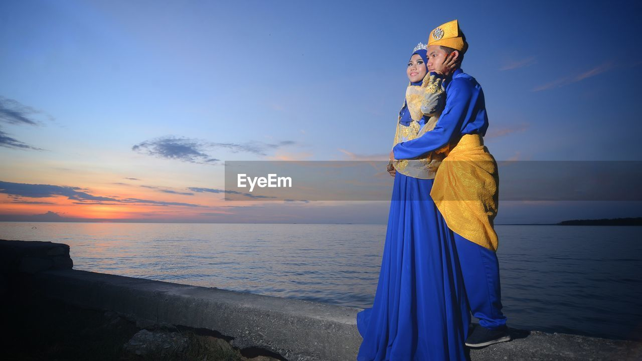 sky, sea, standing, sunset, real people, beach, one person, traditional clothing, full length, horizon over water, blue, outdoors, lifestyles, cloud - sky, water, young women, nature, beauty in nature, women, young adult, scenics, day, people