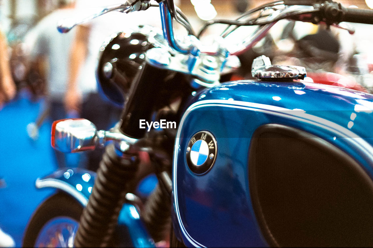 mode of transport, transportation, land vehicle, motorcycle, stationary, handlebar, headlight, blue, focus on foreground, close-up, car, bicycle, retro styled, day, scooter, no people, outdoors, speedometer