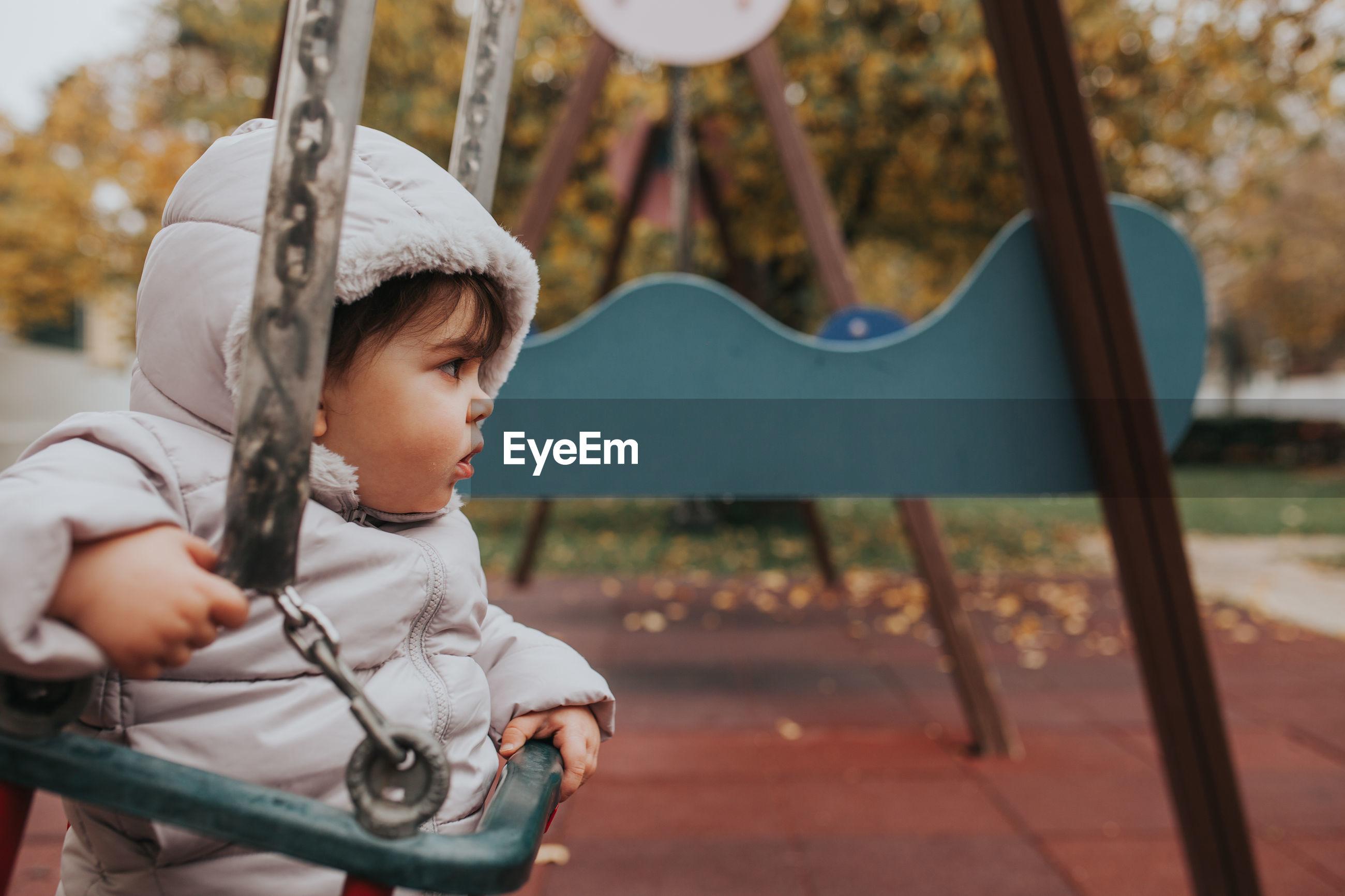 Baby girl sitting on swing at playground