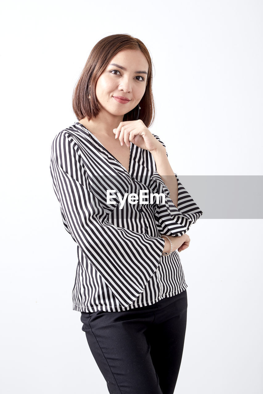 white background, studio shot, looking at camera, indoors, three quarter length, one person, young adult, young women, portrait, striped, beauty, standing, beautiful woman, front view, casual clothing, women, cut out, adult, hairstyle