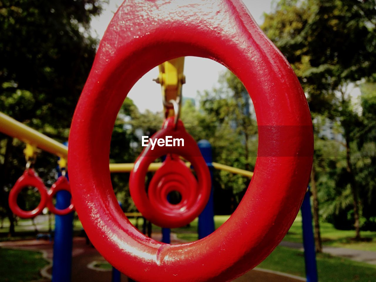 red, metal, playground, circle, valve, outdoor play equipment, no people, park - man made space, day, pipe - tube, outdoors, focus on foreground, close-up, tree, water, nature, water pipe