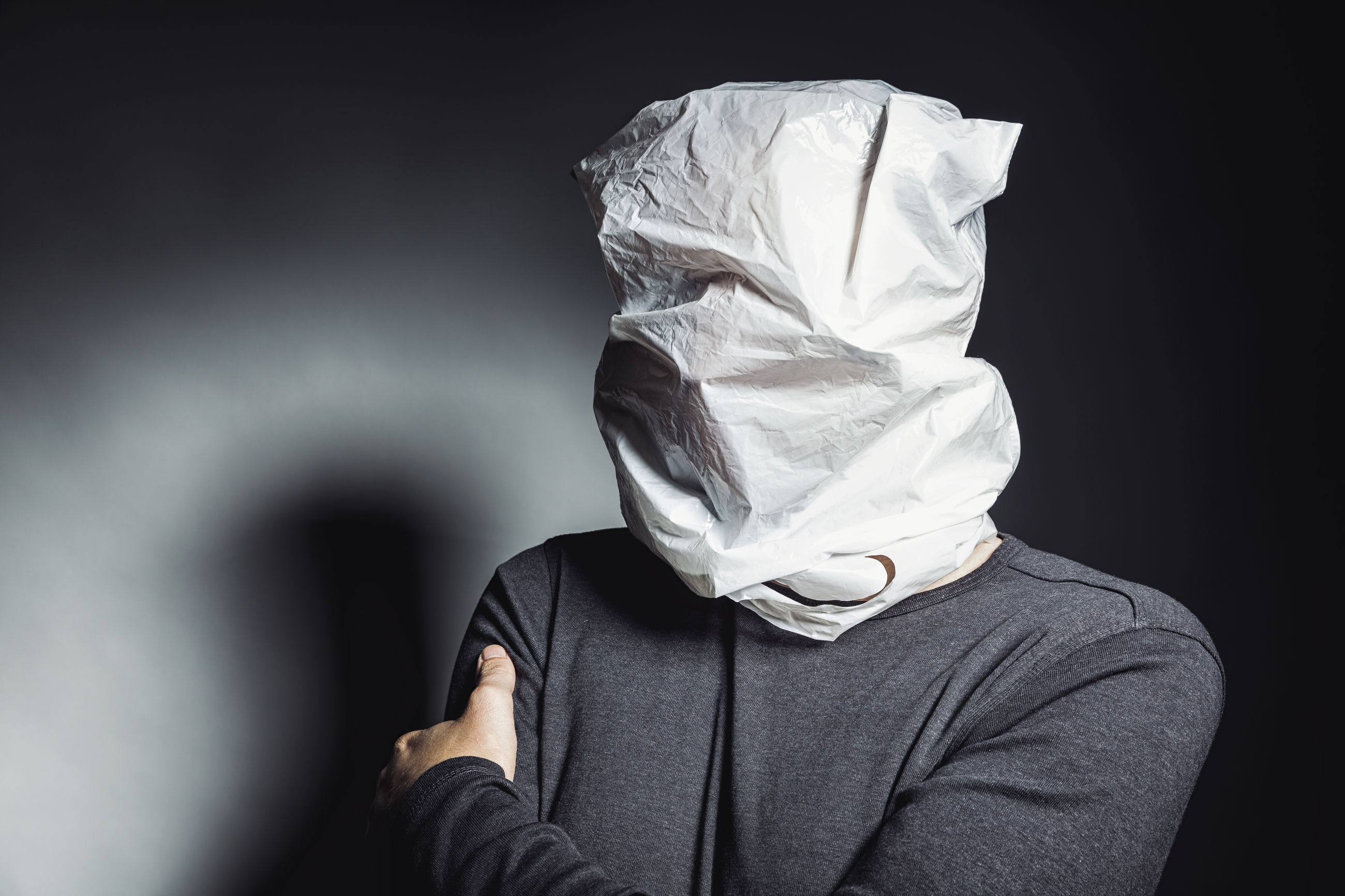 Close-up of woman wearing plastic bag in head against black background