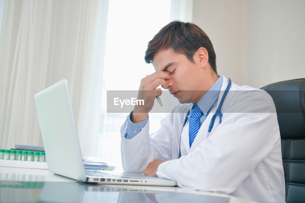 Doctor with laptop working in hospital