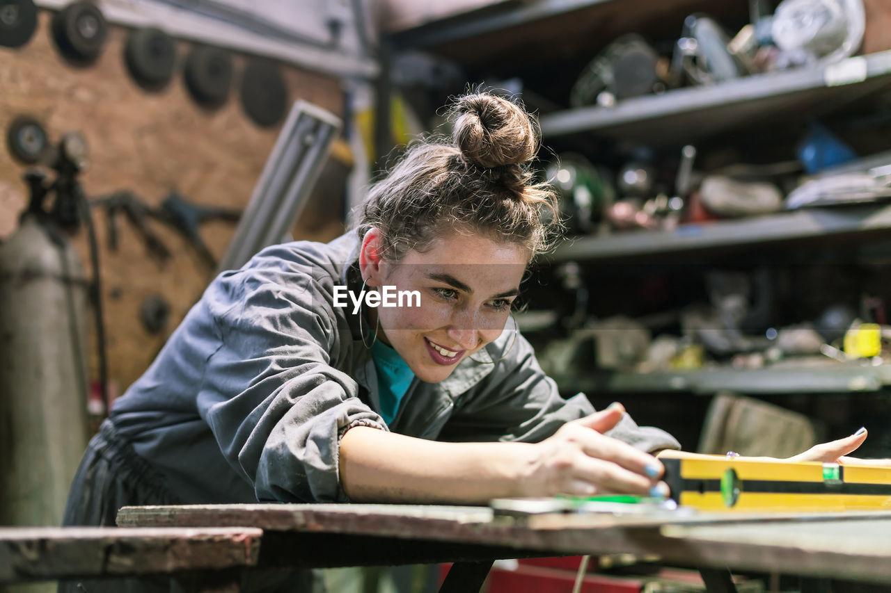 Smiling Manual Worker Working In Workshop