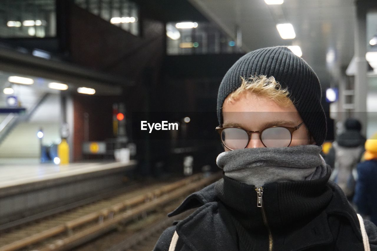 Close-Up Of Man Wearing Turtleneck While Standing At Illuminated Subway Station