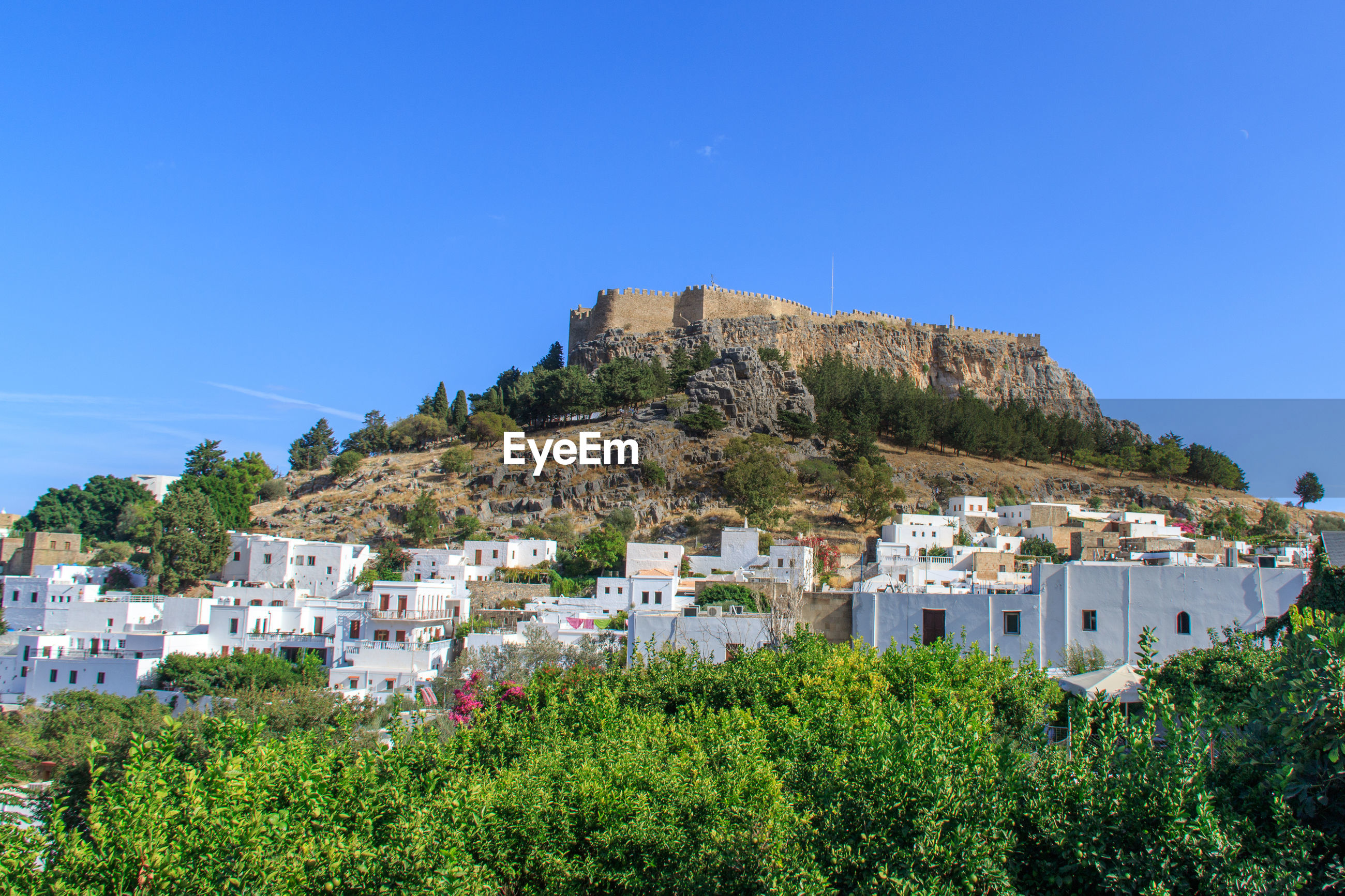 Low angle view of village with castle against blue sky