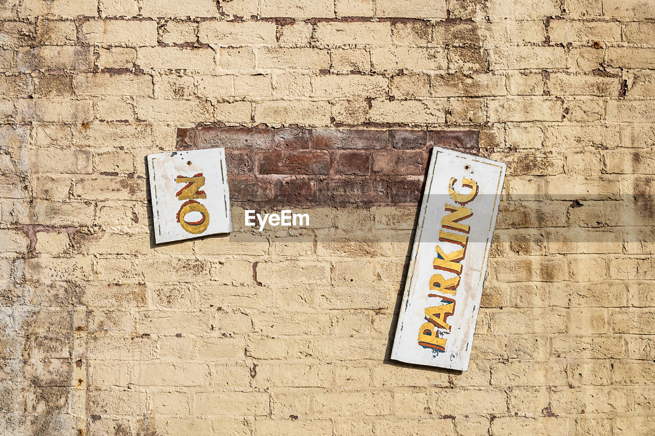 Broken Information Sign Hanging Against Brick Wall