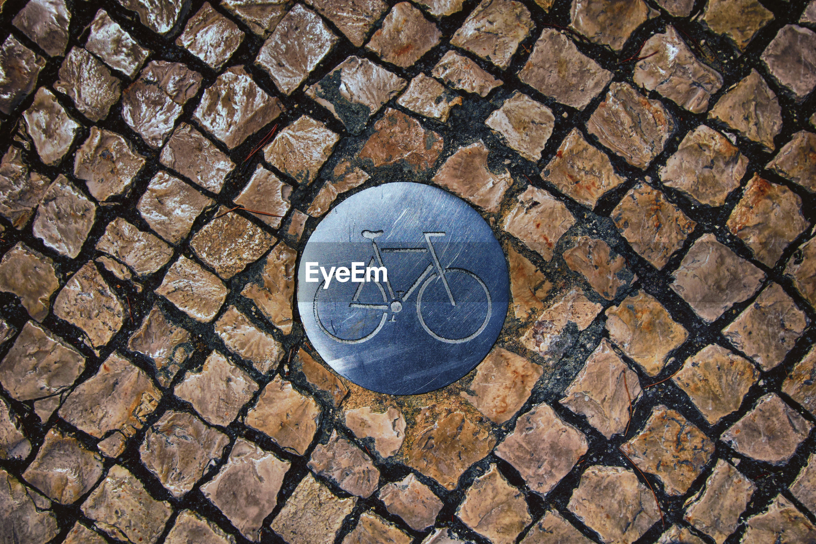 High angle view of bicycle sign on paving stone street in barcelona