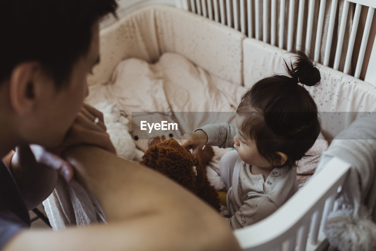 HIGH ANGLE VIEW OF MOTHER AND DAUGHTER RELAXING ON FLOOR