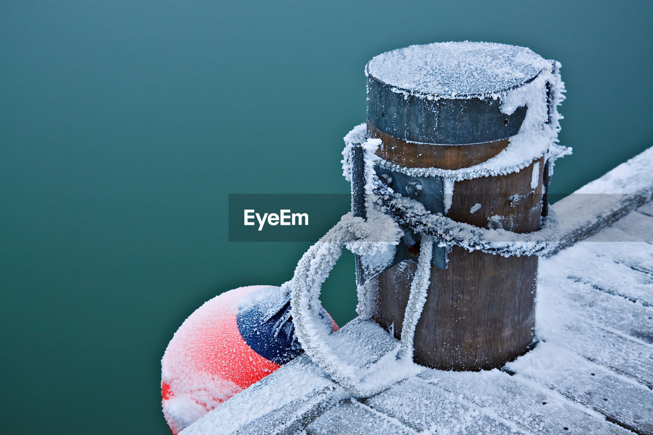 High Angle View Of Frosted Bollard And Buoy By Lake